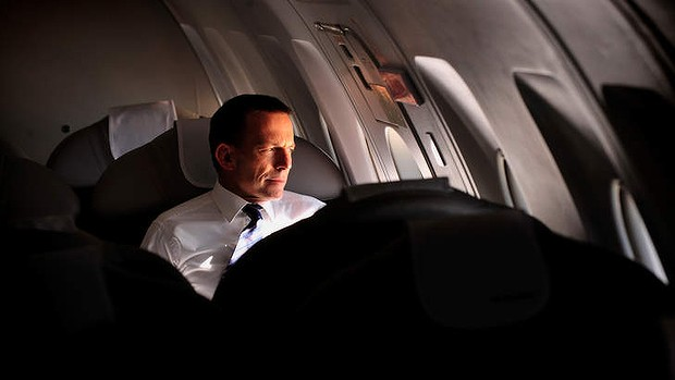 Tony Abbott appears to look out the closed window of a private jet whilst shining a light into his own face